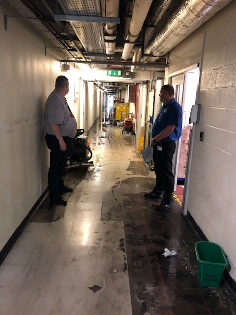 Picture of two men stood in a corridor